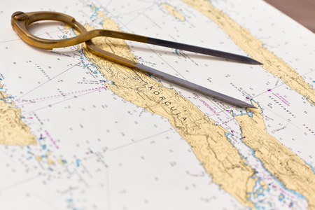 Photo pour Pair of compasses for navigation on a sea map with low depth of field - image libre de droit