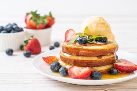 Photo pour souffle pancake with blueberries, strawberries, honey and vanilla ice-cream - image libre de droit