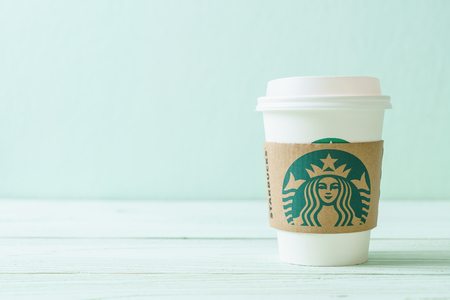Photo pour BANGKOK, THAILAND - JUN 5, 2018: White coffee cup with Starbucks logo on wood background. Starbucks is the world's largest coffee house with over 20,000 stores in 61 countries. - image libre de droit