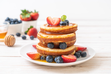 Foto de souffle pancake with fresh blueberries, fresh strawberries and honey - Imagen libre de derechos