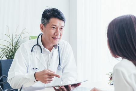 Photo pour Asian doctor and patient are discussing something while sitting at the table - image libre de droit
