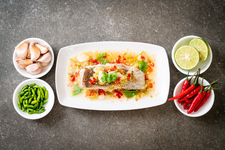 Foto de Steamed Grouper Fish Fillet with Chili Lime Sauce in lime dressing - Asian food style - Imagen libre de derechos