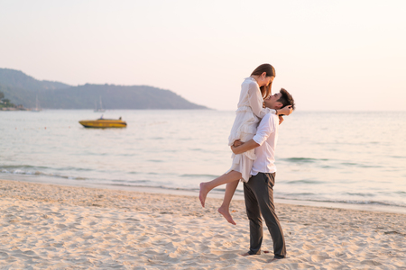 Photo for Happy Asian couple going honeymoon travel on tropical sand beach in summer - Royalty Free Image