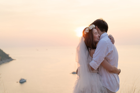 Foto de Happy young Asian couple in love having a good time with sea background - Imagen libre de derechos
