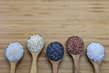 Foto de Variety of rice in wood spoon on wood background. From left: Japanese rice, pounded brown rice, forbidden rice (riceberry), pounded red rice, jasmine rice - Imagen libre de derechos