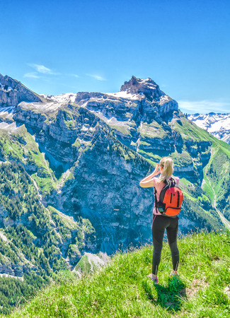 Foto de Traveler screams against the backdrop of the mountain peaks, the Engelberg resort, Switzerland - Imagen libre de derechos