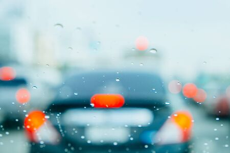 selective focus rain drop shoot inside car with blurred car lights background