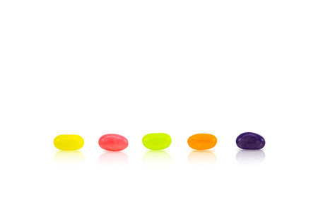 Photo for Color jelly beans are lined up in rows on white background. Conceptual sort by order. - Royalty Free Image