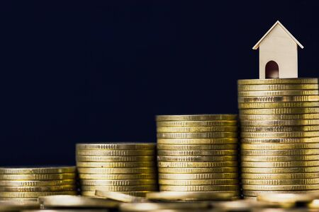 Photo pour Home loan, mortgages, debt, savings money for home buying concept. A small house model on rising stack of coins with black background. Exchange of finances and houses. - image libre de droit