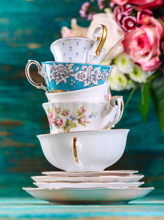 Foto de Stack of vintage tea cups on turquoise background - Imagen libre de derechos