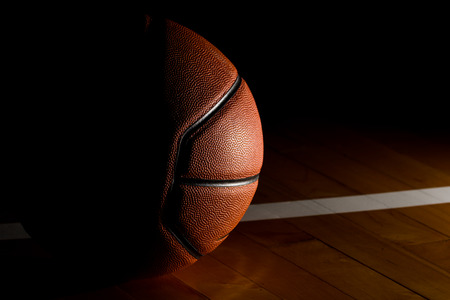 Photo pour Basketball isolated on court black background with light effect - image libre de droit