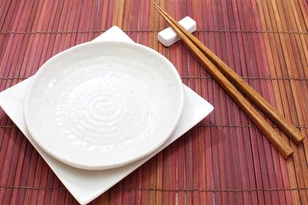 White empty plate with chopsticks