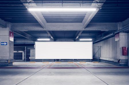 Foto de Parking garage underground interior with blank billboard - Imagen libre de derechos
