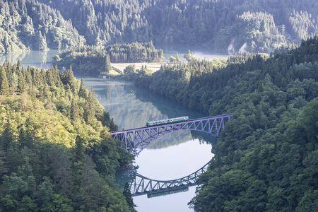 Foto de Fukushima, JAPAN - June 17 : The local train Tadami line and Tadami river on June 17 , 2017 in Fukushima , Japan. This train services in East Japan railway company's Tadami line. - Imagen libre de derechos