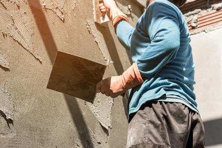 Photo for plasterer concrete worker at wall of house construction - Royalty Free Image
