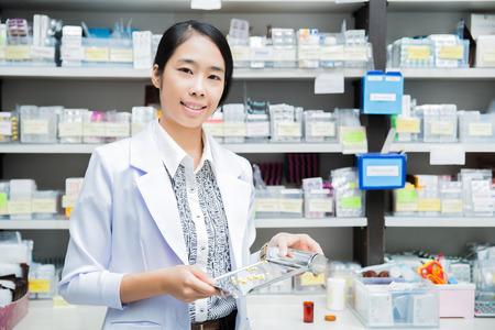 Foto de women pharmacist pharmacy pouring drugs into Tray - Imagen libre de derechos