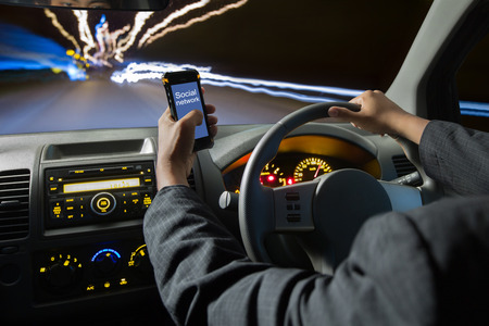 Photo for Man using smart phones while driving at night ,Driving at high speed - Royalty Free Image