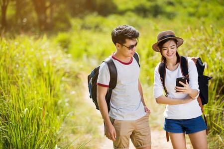 Photo pour Asian tourists Are viewing the maps in mobile phones. - image libre de droit