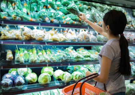 Photo pour Woman are choosing vegetable in supermarket - image libre de droit