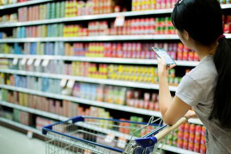 Photo for Woman using phone in supermarkets check to buy - Royalty Free Image
