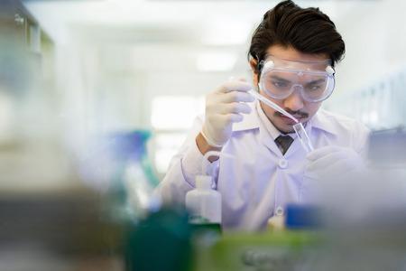 Foto de Asian scientist  in the laboratory working at lab with test tubes - Imagen libre de derechos