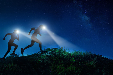 Foto de Night trail runner of men and women running on the mountain.at night milky way - Imagen libre de derechos