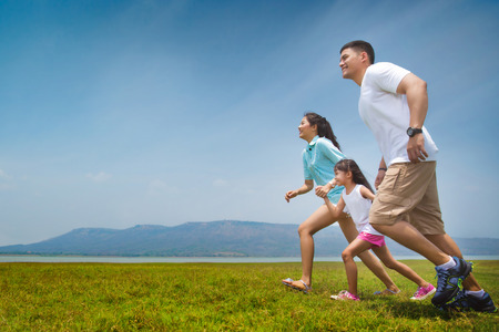 Foto de Asian family running on open grasslands. - Imagen libre de derechos