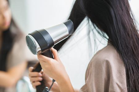 Photo pour Woman with a hair dryer to heat the hair. - image libre de droit
