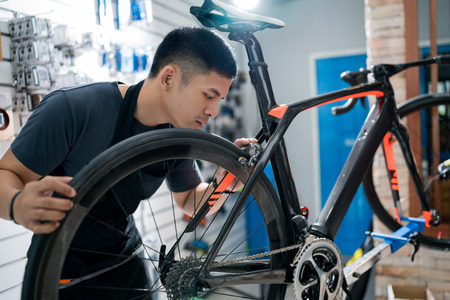 Photo pour Technicians are repairing bicycles at shop sells - image libre de droit