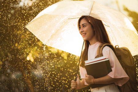 Asian student  waiting for the rain, she had an umbrella.