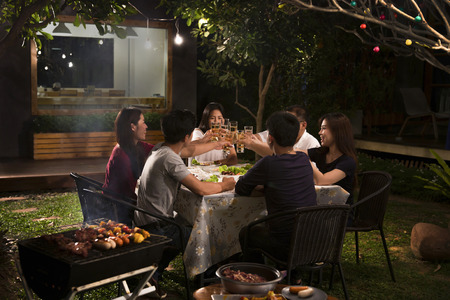 Foto de Dinner party, barbecue and roast pork at night - Imagen libre de derechos