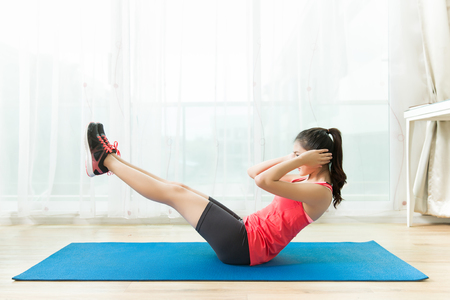 Photo for Asian women are exercising at home.Abdominal exercises Sit ups. - Royalty Free Image