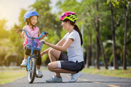 Photo pour The asian family mother teaching children bicycle at the park - image libre de droit