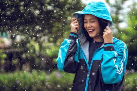 Photo pour Asian woman wearing a raincoat outdoors. She is happy. - image libre de droit