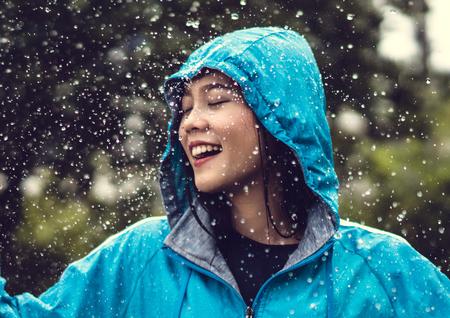 Foto de Asian woman wearing a raincoat outdoors. She is happy. - Imagen libre de derechos