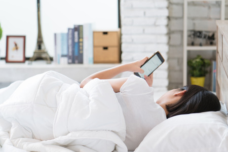 Photo pour Asian girl she is relaxing, she is playing mobile phone in bed. - image libre de droit