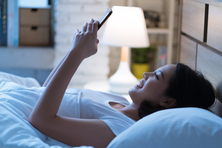 Photo pour Asian women are using the smart phone on the bed before she sleeping at night. Mobile addict concept. - image libre de droit
