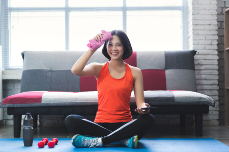 Photo pour Asian woman wiping her sweat after a workout at home. - image libre de droit