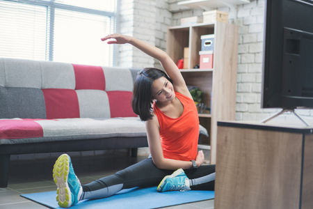Foto de Asian women she is exercising at home. she is doing the exercises she looks at on TV. - Imagen libre de derechos