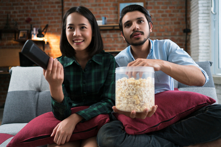 Foto de Couple watching movie at home happily. They sit on sofa, eat soft drinks and popcorn while watching movies. - Imagen libre de derechos
