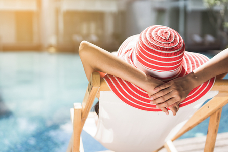 Foto de Woman is sitting in a chair relaxing in the summer, she is in the pool. - Imagen libre de derechos
