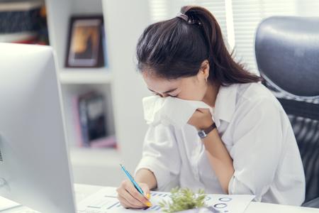 Foto de Women are sneezing and are cold. She is in the office. - Imagen libre de derechos