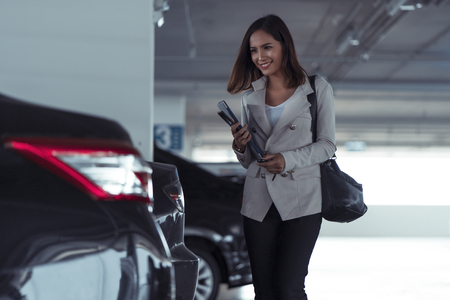 Photo for business woman asian is opening the car with a remote key, she is going home. - Royalty Free Image
