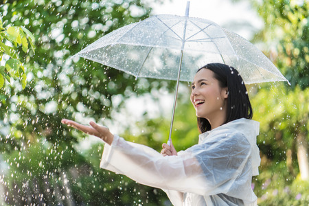 Foto de Rainy day asian woman wearing a raincoat outdoors. She is happy.She used her hand to touch the rain. - Imagen libre de derechos