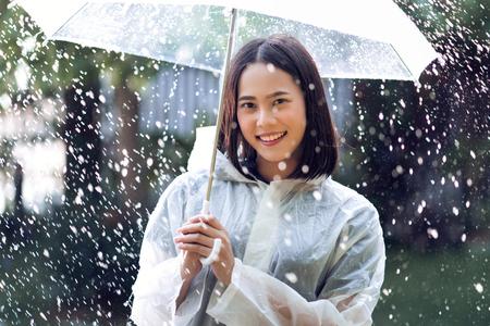 Photo pour Rainy day asian woman wearing a raincoat outdoors. She is happy. - image libre de droit