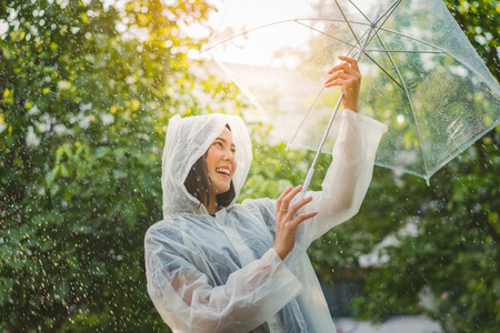 Foto de Rainy day asian woman wearing a raincoat outdoors. She is happy. - Imagen libre de derechos