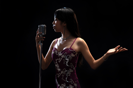 Photo for Asian woman singer holding a microphone singing. - Royalty Free Image