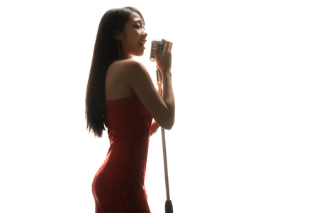 Foto per Asian woman singer holding a microphone singing. - Immagine Royalty Free