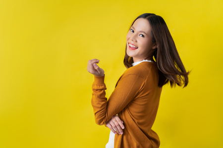 Foto de happy asian woman in yellow background - Imagen libre de derechos