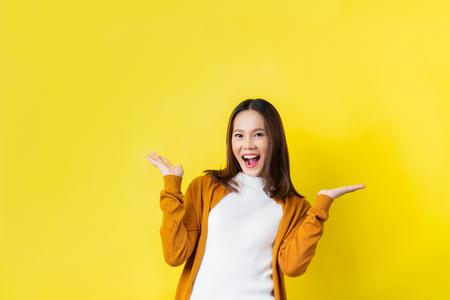 Foto de Asian girl is surprised. She is excited.Yellow background studio - Imagen libre de derechos